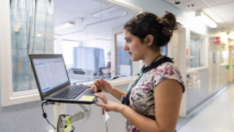 A member of staff standing at a computer on a hospital ward